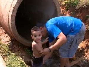 Criança toma banho em bica em Itu (Foto: Reprodução/TV TEM)