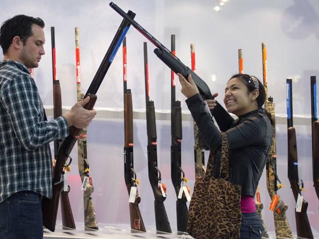 Casal olha armamentos durante evento (Foto: Reuters)