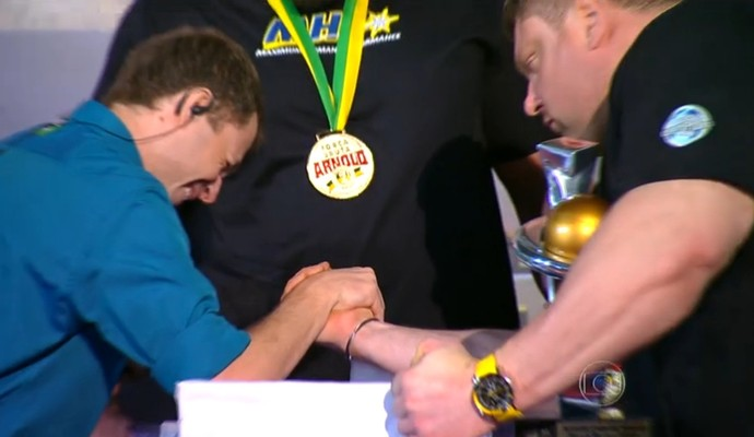 Tiago Leifert disputa queda de braço com o lituano Zydrunas Savickas, campeão do Força Bruta (Foto: Reprodução TV Globo)