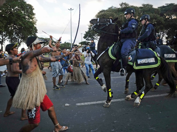 Indígena atira flecha contra policial durante protesto em Brasília nesta terça-feira (27). (Foto: Lunae Parracho/Reuters)