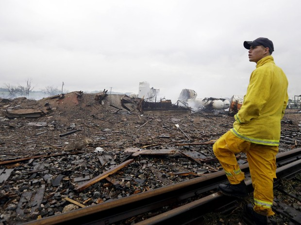 à beira de uma linha ferroviária, bombeiro observa a área devastada pela explosão em West (Foto: LM Otero/AP)