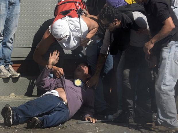 Pessoas ajudam um homem ferido durante protesto da oposição ao governo do presidente da Venezuela, Nicolas Maduro, em Caracas. (Foto: Juan Barreto/AFP)
