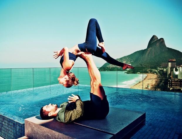 Com a praia de Ipanema ao fundo, a atriz Manuela Mesquita e o artista circense Bruno Carneiro posam para Vogue fazendo a posição Black Bird da acroioga  (Foto: Renata Chede/Arquivo Vogue)