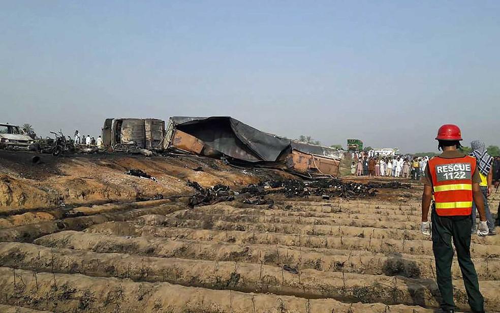 Socorrista observa corpos queimados depois que um caminhão-tanque sofreu acidente e pegou fogo no Paquistão (Foto: STR / AFP Photo)