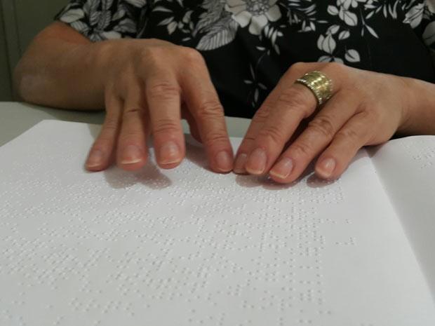 Muher com deficiência visual lê livro em Braille em biblioteca de Taguatinga, no Distrito Federal (Foto: Raquel Morais/G1)