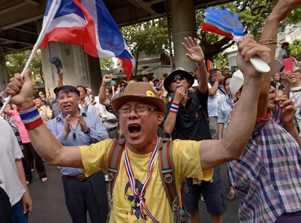 Manifestante acena com bandeiras durante protesto contra premiê do país (Foto: PORNCHAI KITTIWONGSAKUL/ AFP)