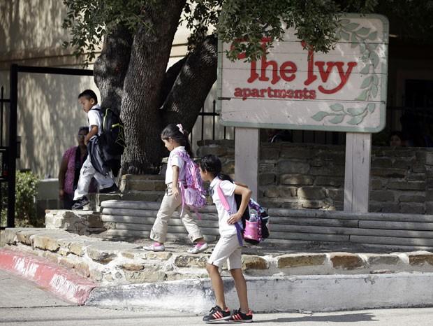 """Criança passa em frente à placa do hotel """"The Ivy"""", em Dallas, onde ambulância pegou um homem que foi diagnosticado com Ebola (Foto: Mike Stone/Reuters)"""