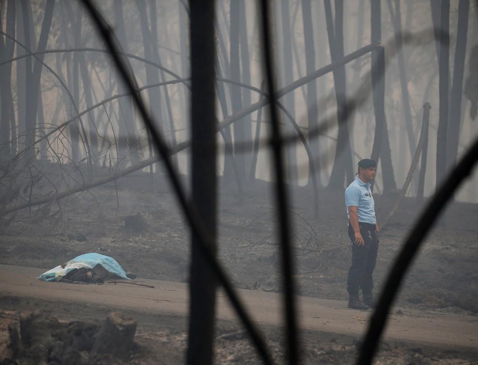 Policial guarda corpo de uma das vítimas do incêndio florestal na autoestrada IC8, perto de Pedrógão Grande, na região central de Portugal (Foto: Rafael Marchante)