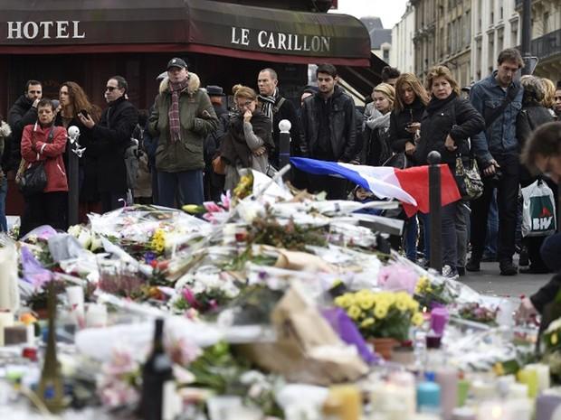 Pessoas fazem um minuto de silêncio em frente ao restaurante Le Carillon, na esquina das ruas Bichat e Alibert, em Paris. O restaurante foi alvo dos ataques (Foto: Eric Feferberg / AFP)