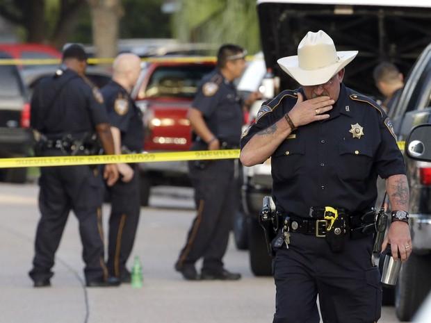 O sargento do condado de Harris, D.J. Hilborn, deixa a cena do crime neste domingo (Foto: AP)