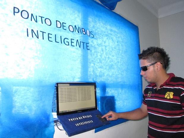 Estudante simula a utilização do ponto de ônibus inteligente (Foto: Mariane Rossi/G1)
