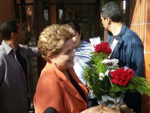 Apoiadores esperaram a presidente em frente à residência para entregar flores de Dia das Mães  (Foto: Juliano Posada Chimenes/RBSTV)