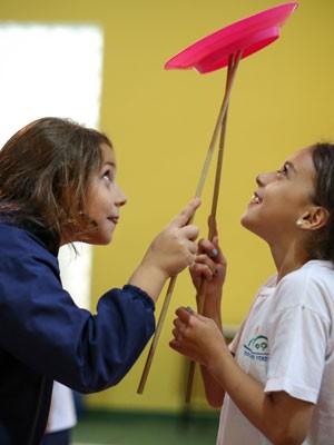 Rafaella e Luana equilibram um prato de plástico giratório (Foto: Raul Zito/G1)