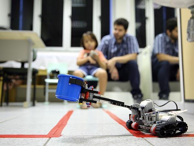 A criança controla o robô durante um jogo, que é dividido em fases de acordo com o nível de dificuldade, indo desde a montagem da máquina até controlá-la para pegar objetos (Foto: Ares Soares/Unifor)