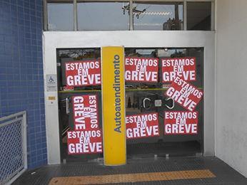 Grevistas colocaram cartazes nas portas das agências (Foto: Gesseca Ronfim/G1 MT)