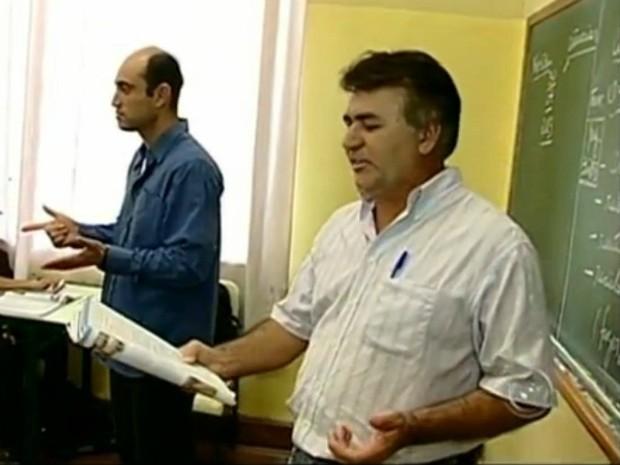 Ao lado do professor, intérprete repassa as explicações ao aluno com surdez. (Foto: Reprodução TV TEM)