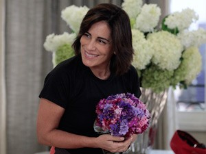 A viúva fica toda derretida com as flores que recebe do gato (Foto: Guerra dos Sexos/ TV Globo)