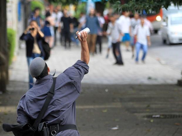 Policial atira lata de gás lacrimogêneo contra estudantes da Escola Estadual Fidelino Figueiredo que bloquearam o cruzamento das avenidas São João e Angélica, na Zona Oeste de São Paulo (Foto: Werther Santana/Estadão Conteúdo)