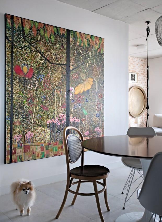 Entrada. Amelie, cadela de estimação de Naiana, dá as boas-vindas à frente da tela do artista goiano Gustavo Rizerio, que inspirou a paleta de cores do apartamento (Foto: Marco Antonio / Editora Globo)