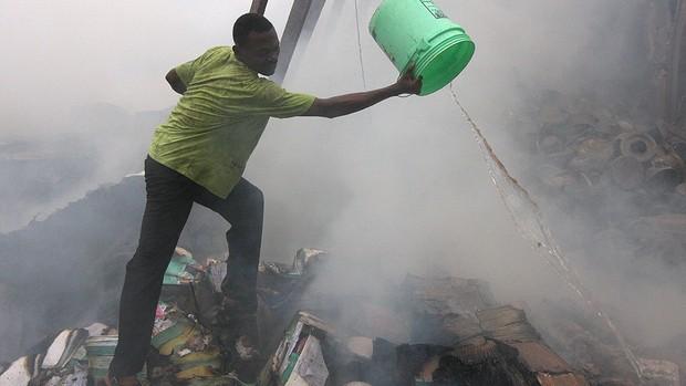 Usando apenas um balde, nigeriano tenta conter o fogo provocado pelo acidente aéreo na Nigéria (Foto: Jon Gambrell/AP)