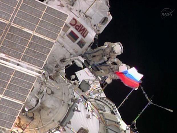Engenheiros de voo Fyodor Yurchikhin e Alexander Misurkin seguram bandeira russa quase no fim da caminhada espacial  (Foto: Nasa TV/Reprodução)