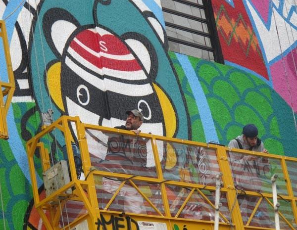 Em cima de um andaime a dez metros do chão, o artista plástico Rui Amaral trabalha no seu mural feito na parede de um prédio na Av. Paulista (Foto: Victória Brotto/G1 SP)