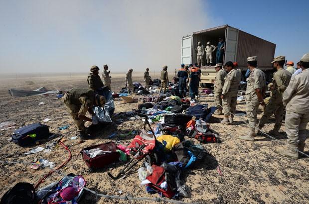 Soldados egípcios recolhem objetos pessoais pertencentes às vítimas do acidente com o avião russo na península do Sinai; a imagem foi divulgada pelo Ministério de Situações Emergenciais da Rússia (Foto: Russian Ministry for Emergency Situations/AP)