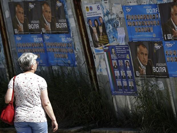 Mulher olha para cartazes eleitorais de Boiko Borisov, líder do partido GERB de centro-direita  na Bulgária, em um subúrbio de Sofia no sábado (11) (Foto: REUTERS / Stoyan Nenov )