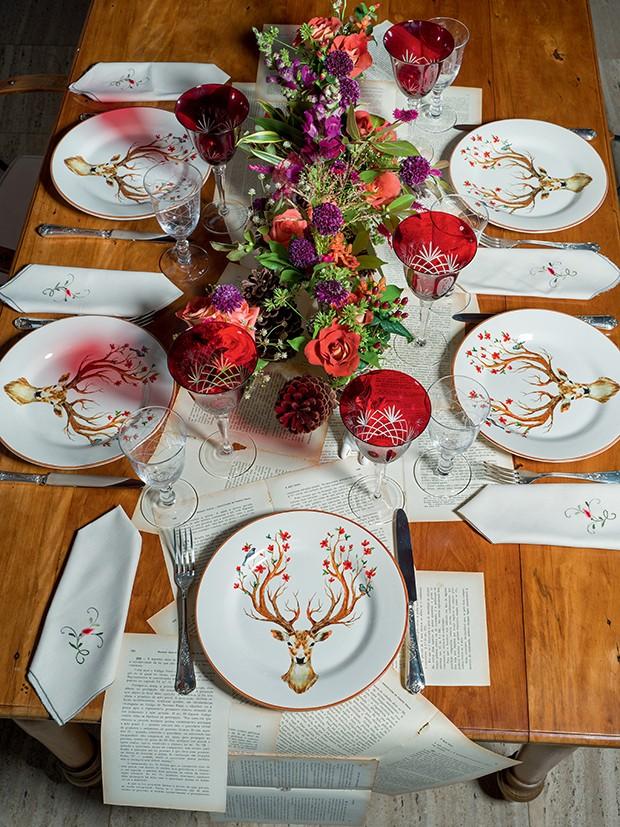 Poucos e bons arranjos  + um belo jogo de louças são suficientes para  a mesa de jantar, que tem como protagonista a passadeira feita com páginas de contos (Foto: .)