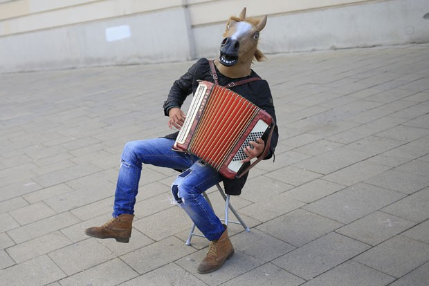 Um artista de rua chamou atenção nas ruas de Viena, na Áustria, ao usar uma cabeça de cavalo enquanto tocava acordeão (Foto: Alexander Klein/AFP)