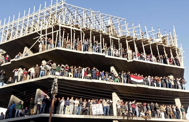 Prédio em contrução fica lotado de pessoas que acompanham o funeral dos mortos em um ataque a bomba a uma central de polícia, nesta terça-feira (24) (Foto: Mohamed Abd El Ghany/Reuters)
