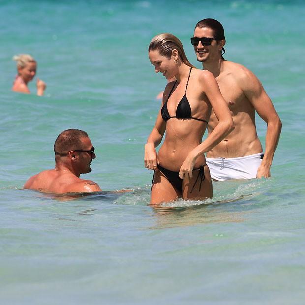 Candice dá uma ajeiadinha no biquíni ao sair do mar (Foto: Splashnews)