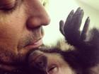 Latino acorda com macaco de estimação grudado no pescoço