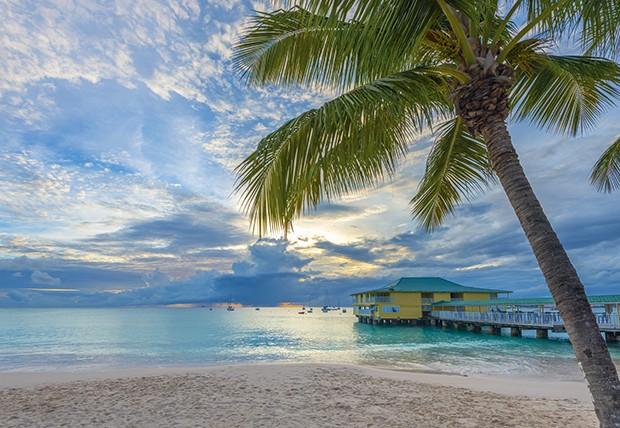 As águas azuis do Caribe e o belo píer da praia de Carlisle. (Foto: Alan Copson/Getty Images)