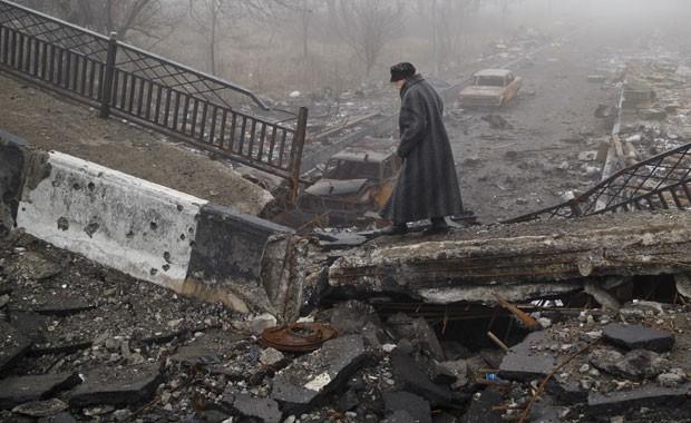 Mulher anda por área destruída por combates em Donetsk neste domingo (1º)  (Foto: Vadim Ghirda/AP)