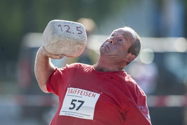 Bruno Batt faz careta ao jogar pedra de 12,5 kg durante campeonato na Suíça (Foto: Keystone,Gian Ehrenzeller/AP)