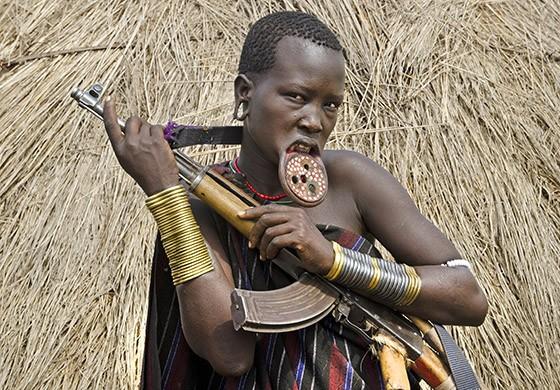Uma jovem mursi com um disco labial ainda de tamanho médio mostra um fuzil AK-47 como símbolo de poder (Foto: © Haroldo Castro/ÉPOCA)