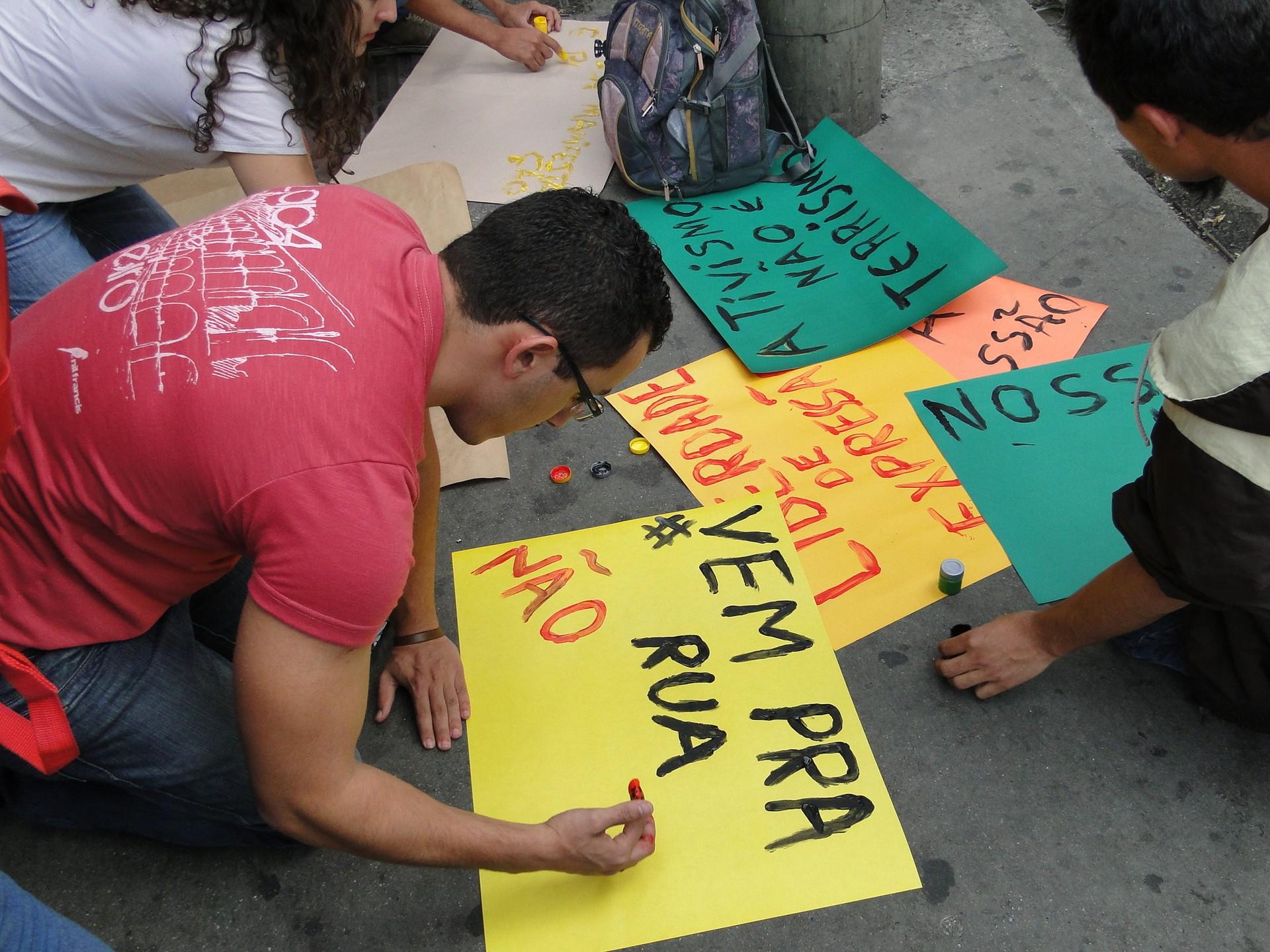 Jovem produz cartaz na manifestação na Praça Sete, em Belo Horizonte (Foto: Raquel Freitas/G1)