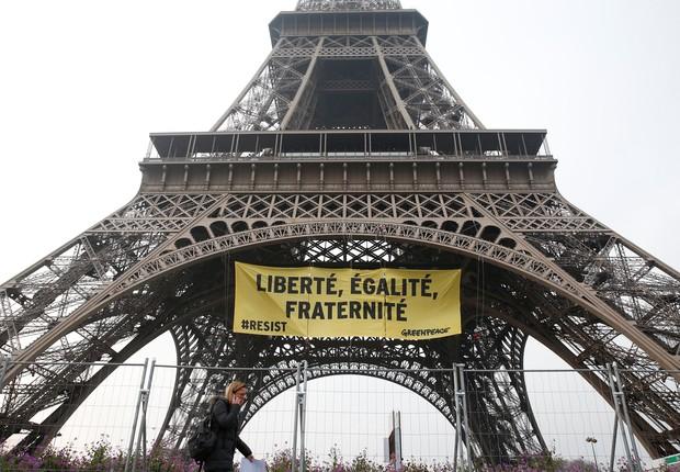 Uma mulher passa pela Torre Eiffel enquanto ativistas do Greenpeace abrem um faixa gigante com mensagem política no monumento, em Paris (Foto: Gonzalo Fuentes/Reuters)