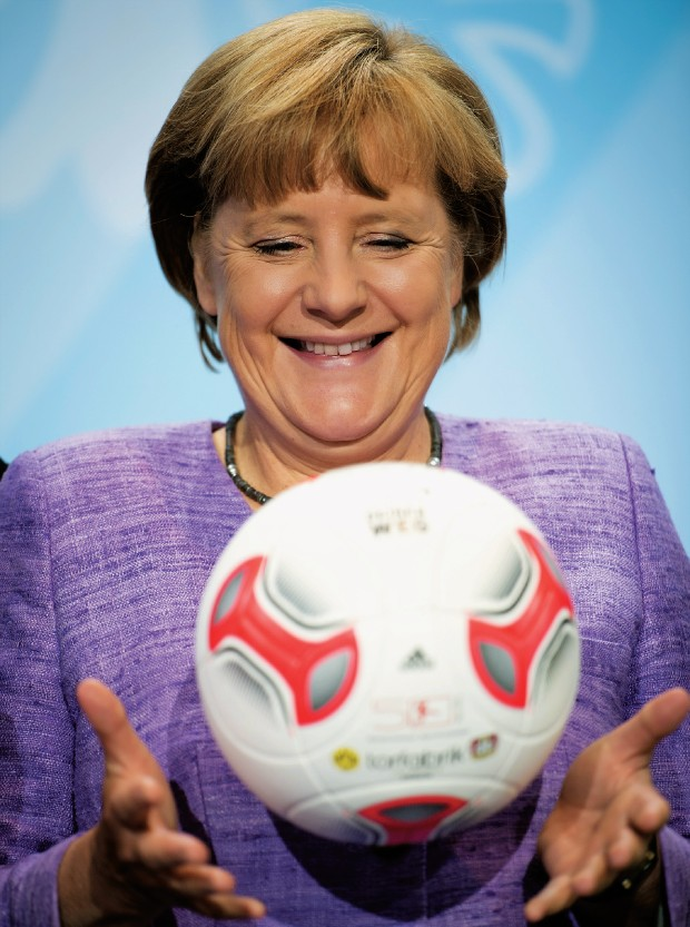 GERMÂNIA futebol clube A chanceler da Alemanha, Angela Merkel, brinca com uma bola durante uma entrevista, em 2012. A gestão mais austera explica o  sucesso dos clubes de futebol alemães (Foto: Odd Andersen/AFP/GettyImages)