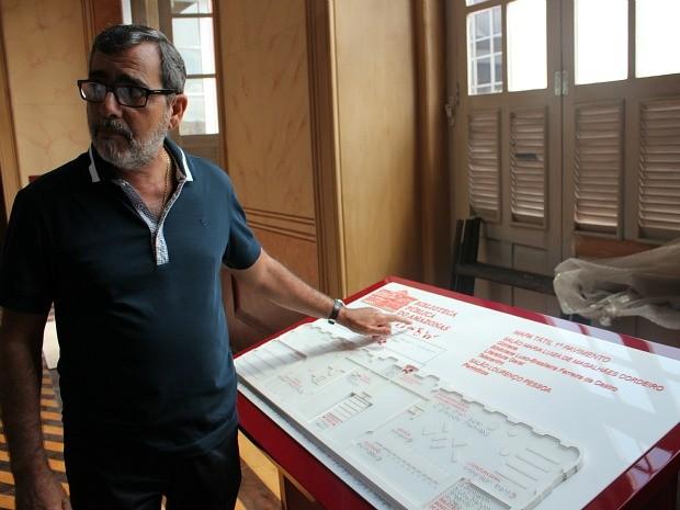 Secretário de Estado de Cultura, Robério Braga, exibe uma das novidades da biblioteca: folheador automático (Foto: Adneison Severiano/G1 AM)
