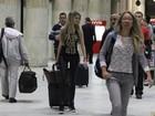 Toda de preto, Barbara Evans desembarca no aeroporto do Rio