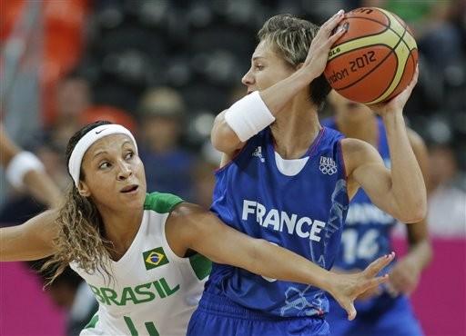 A jogadora francesa Celine Dumerc é marcada por Adriana Pinto no jogo de estreia do basquete brasileiro em Londres 2012 (Foto: Charles Krupa/AP)