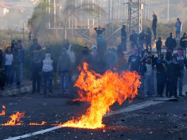 Jovens árabes israelenses entram em choque com a polícia israelense na entrada para a cidade de Kfar Kanna, norte de Israel, neste sábado, 8 de novembro. Milhares foram às ruas no sábado horas depois que o jovem Khayr al-Din al-Hamdan foi baleado pela polícia  (Foto: Ammar Awad/Reuters)