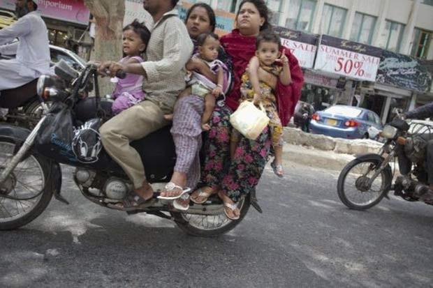 Em julho de 2011, um motociclista foi flagrado carregando outras cinco pessoas de sua família em uma moto na cidade de Karachi, no Paquistão. Entre os seis ocupantes havia dois bebês.  (Foto: Behrouz Mehri/AFP)