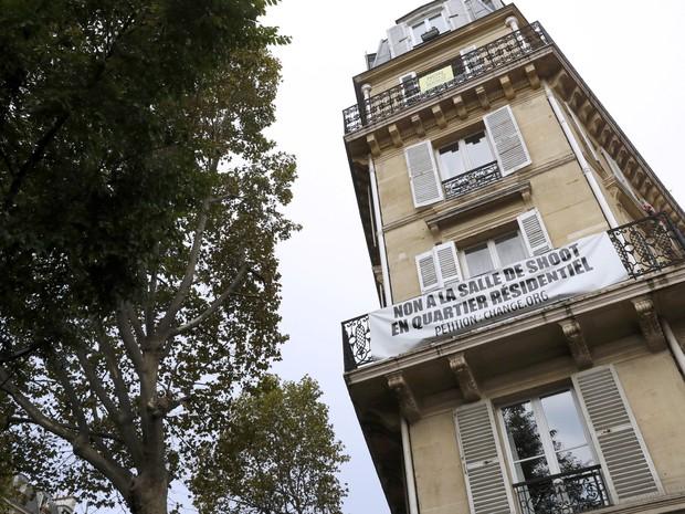 Prédio perto do Hospital Lariboisière exibe faixa de protesto contra o funcionamento da sala de consumo de drogas de menor risco (Foto: PATRICK KOVARIK / POOL / AFP)