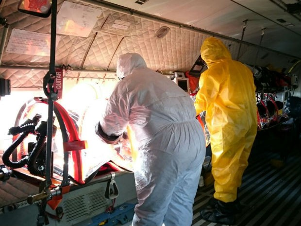 Militares com roupas especiais preparando avião para casos de ataque terrorista (Foto: Mateus Rodrigues/G1)