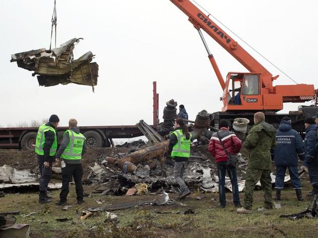 Equipes coletam partes do avião da Malaysia Airlines, voo MH17, neste domingo (16), na Ucrânia (Foto: MENAHEM KAHANA / AFP)