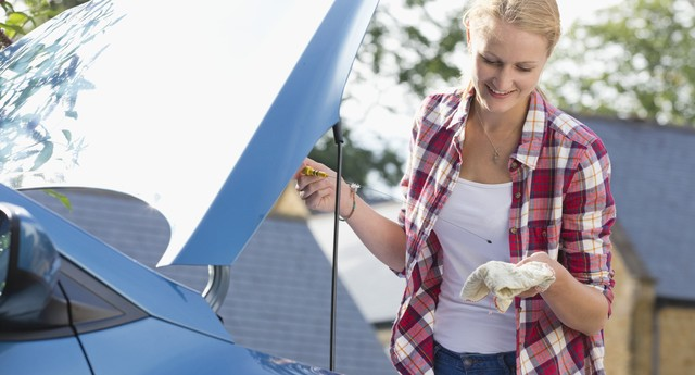 Woman Checking Oil Level In Car Engine (Foto: Getty Images/iStockphoto)