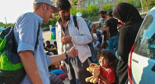 Voluntário dá brinquedo a criança refugiada, à espera do ônibus para Mytilene (Foto: BBC/Stella Chiarelli)